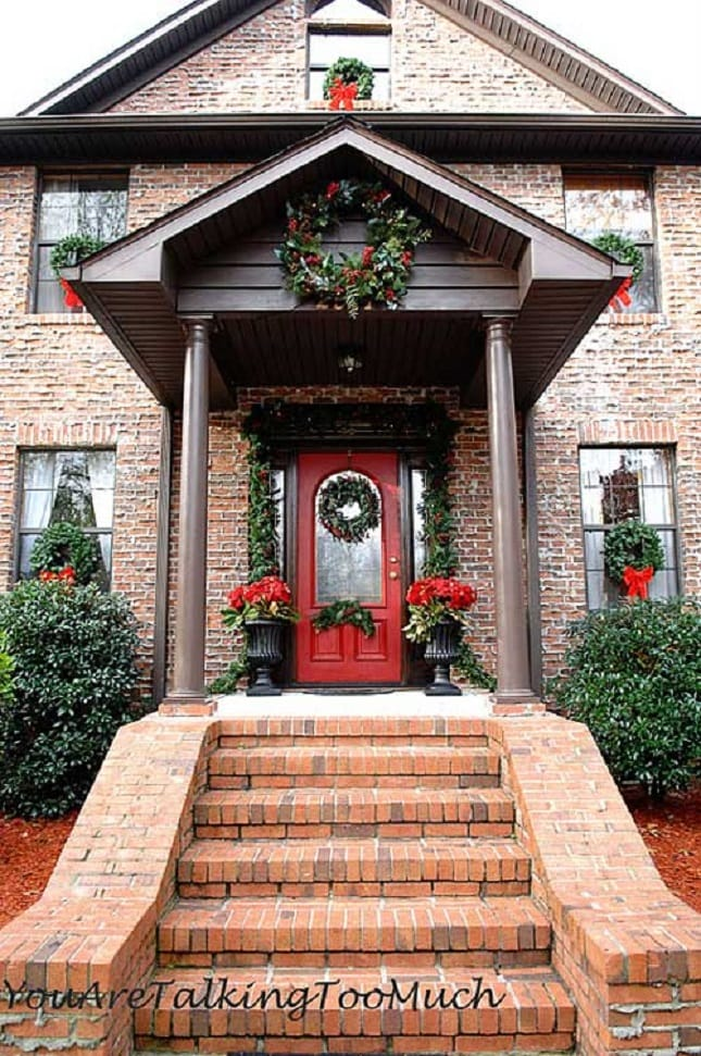 greenery garland red front door front porch christmas