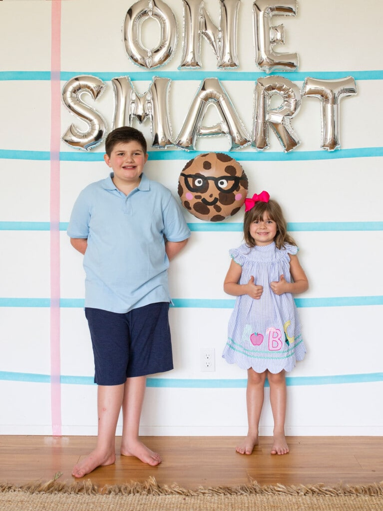 kids in front of note pad backdrop